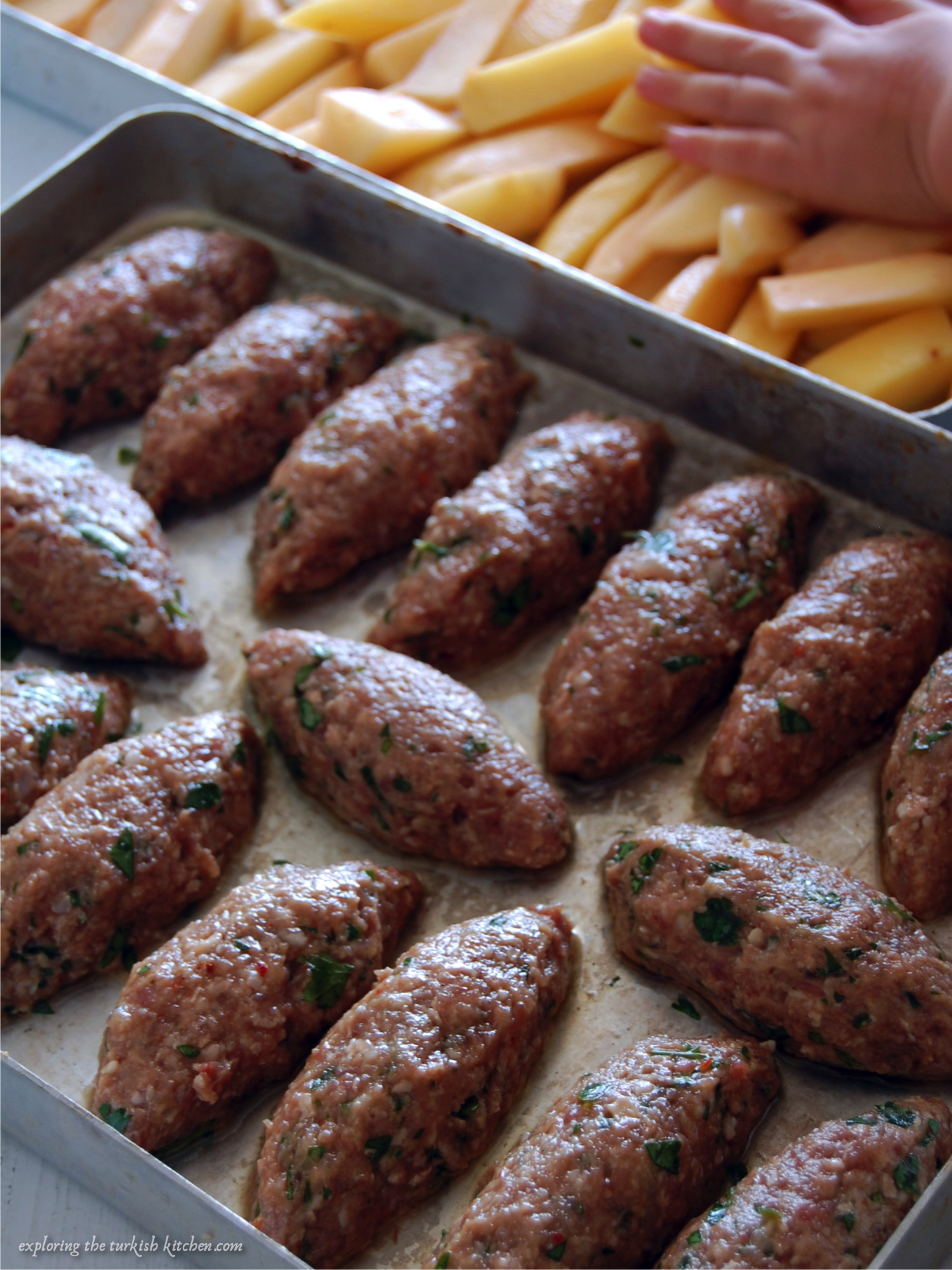 Turkish Izmir style meatballs, long shaped patties lined up on a baking sheet. Potato wedges on tray behind with small child hand patting them down.