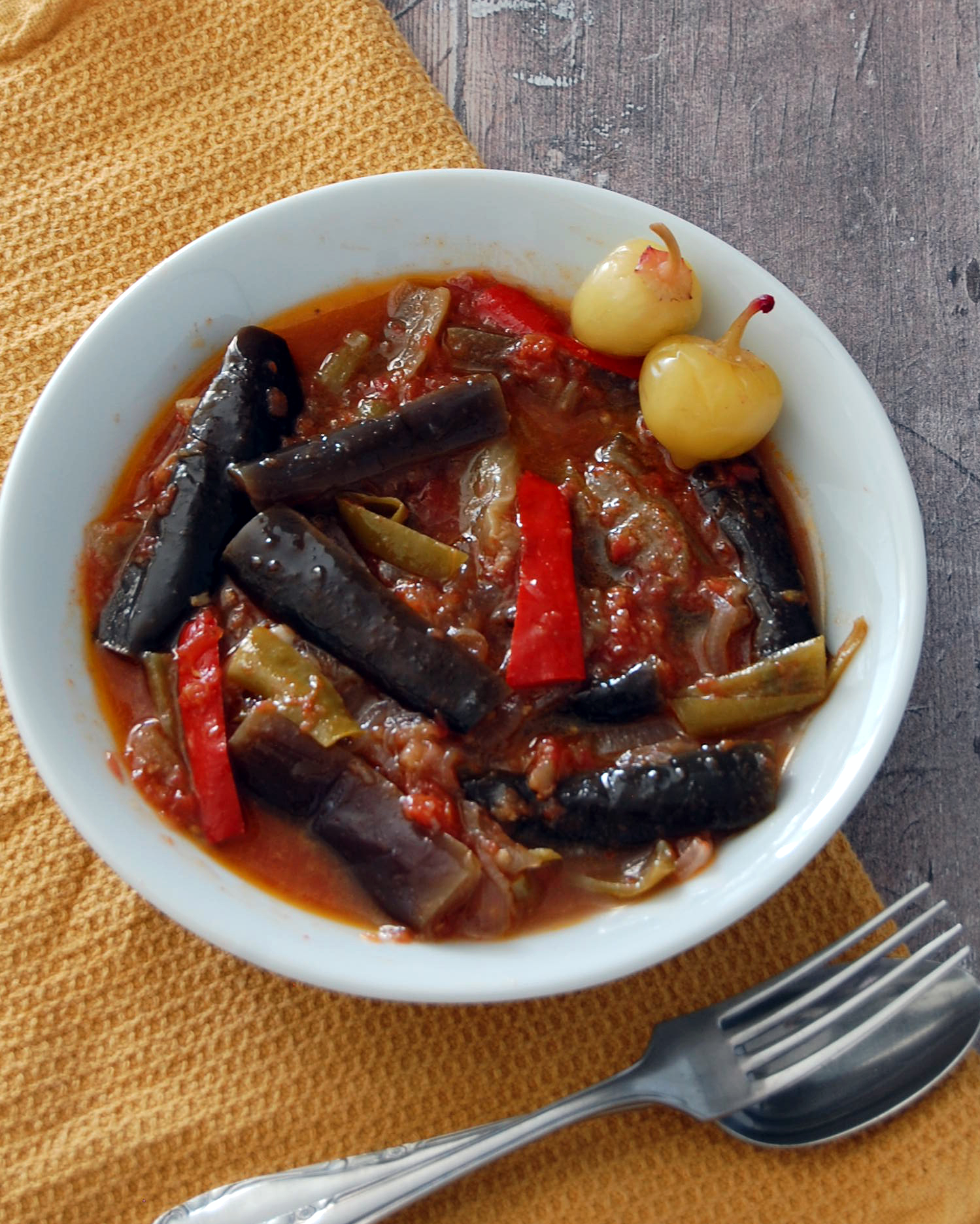 White bowl of aubergine and pepper stew. Two small pickled peppers and yellow hanky.